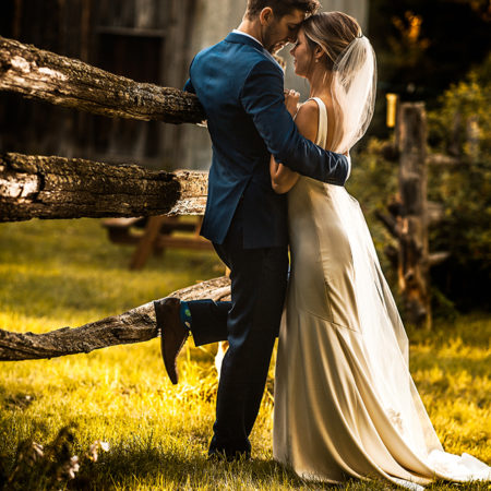 Bride and groom move in close for an intimate farm wedding photo