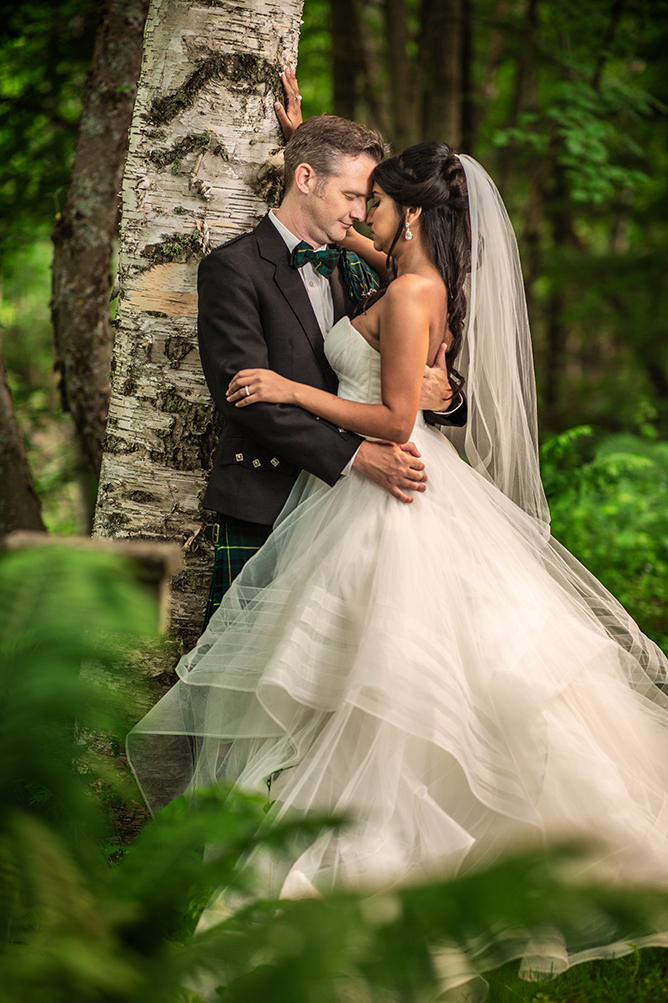 A Bride and groom are photographed while they kiss beside a tree